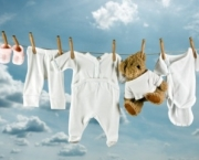 Cute teddy bear hanging outside between baby laundry